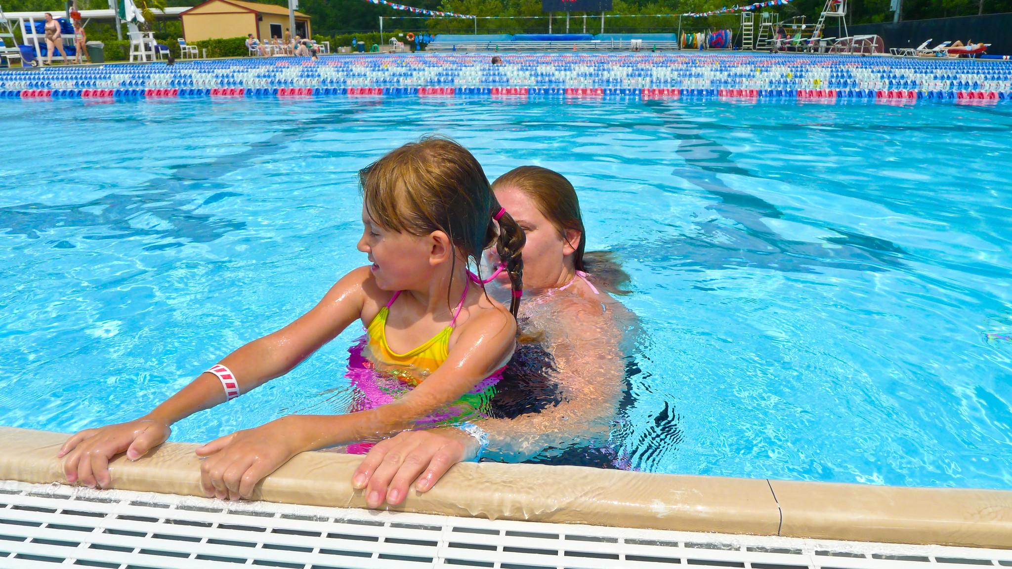Swim Instructor Teaching Girl To Swim