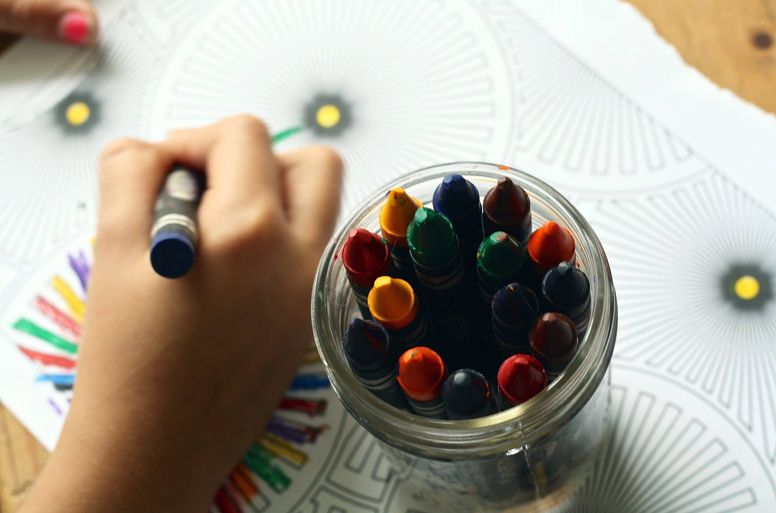 Child Coloring With Crayons