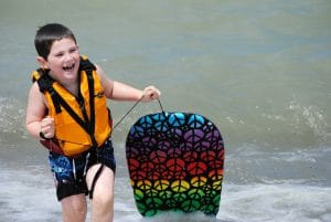 Little Boy Smiling In The BEach While Wearing Swimming Gear For Kids