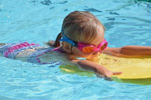 Little Girl Swimming While Using Swimming Gear For Kids