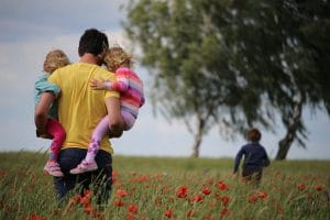 Family Running On A Field With Flowers