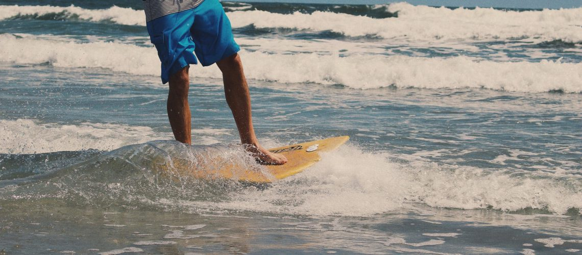 Model Surfing And Showing Off His Swim Trunks